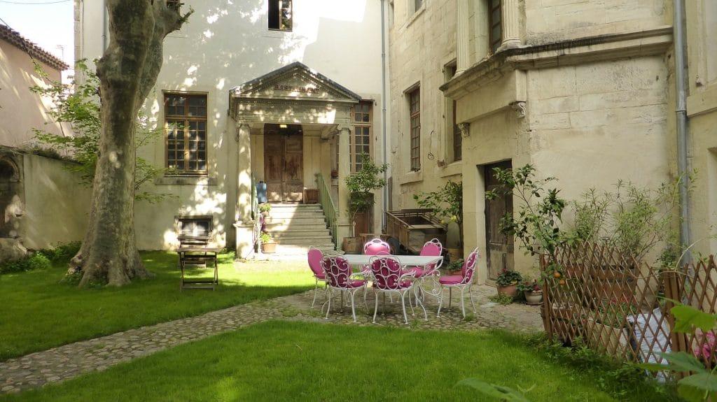 Une cour dans une maison ancienne avec un jardin gazon