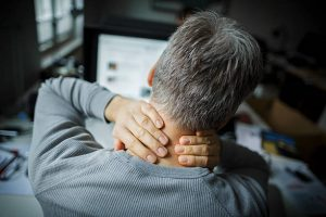 Homme de dos se tenant la nuque à cause d'une douleur aux cervicales