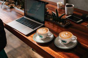 Tasses de café sur un bureau en bois à côté d'un ordinateur
