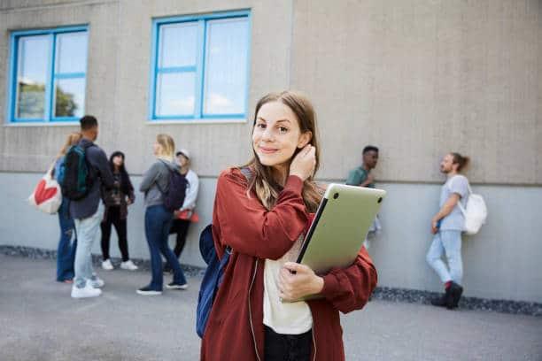Jeune étudiante qui sourie à la caméra et qui porte un ordinateur portable dans ses bras