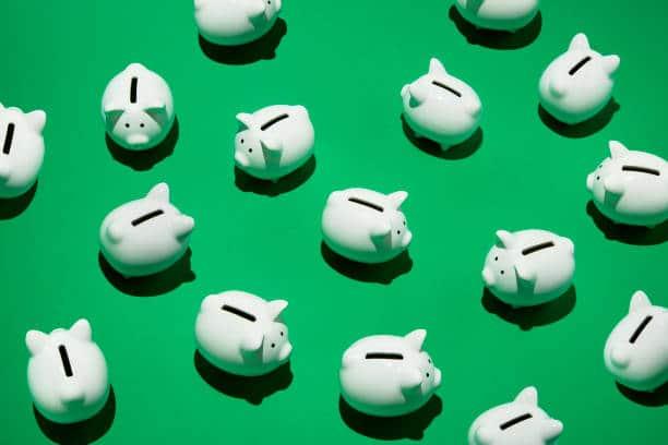 Plusieurs petites tirelires blanches sur fond vert