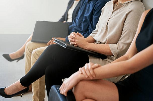 Gros plan sur trois personnes qui attendent dans une salle d'attente avant un entretien