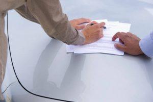 Personnes en train de signer une vente sur le capot d'une voiture d'occasion