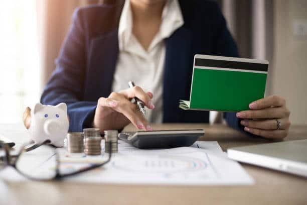 Femme qui calcule des frais avec une calculatrice et un chéquier dans la main