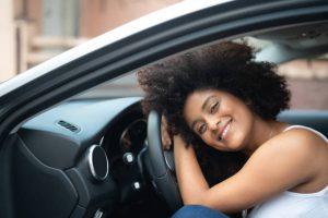 Jeune femme souriante appuyée contre le volant d'une voiture d'occasion