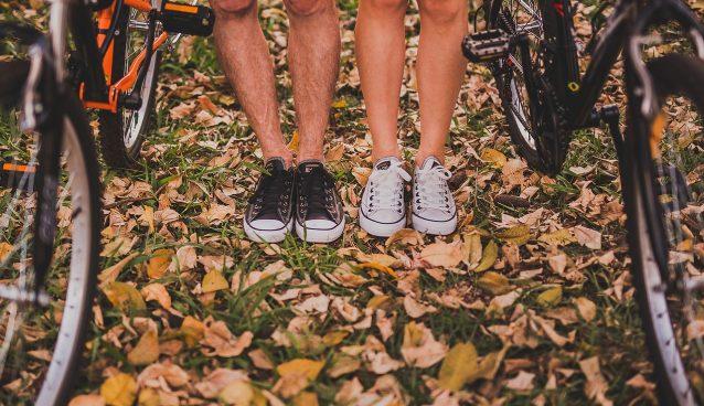 homme et femme près de vélos portant des converses sur un sol avec feuilles mortes