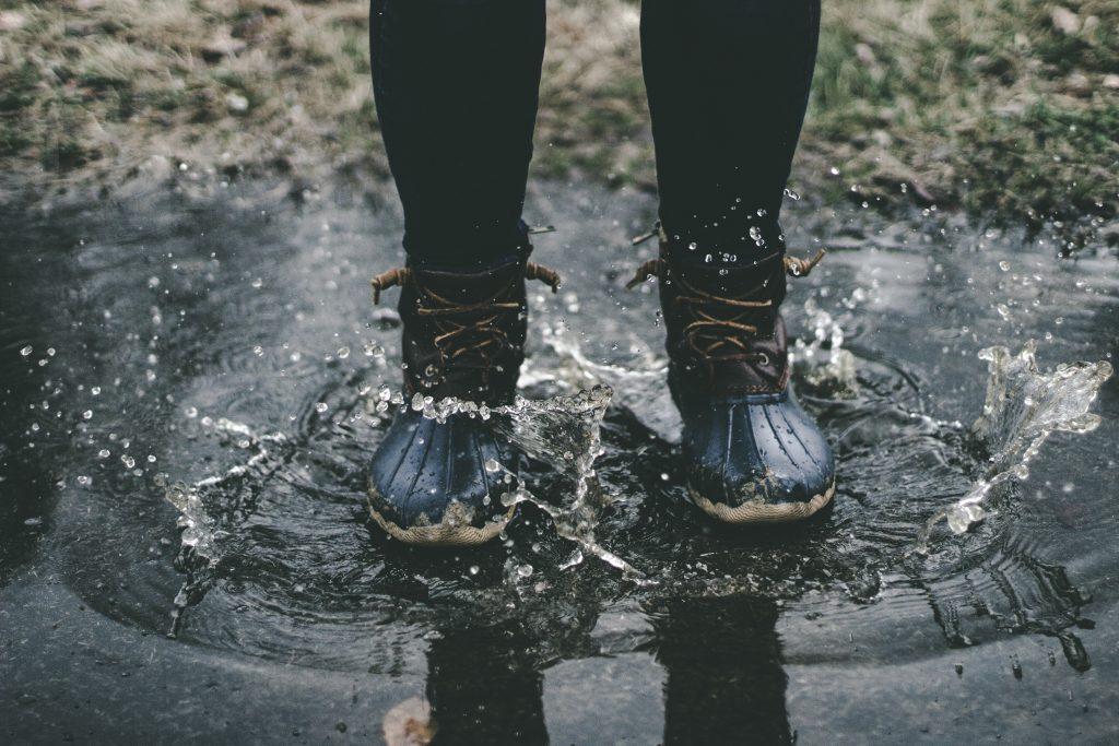 personne portant des boots noires dans une flaque d'eau