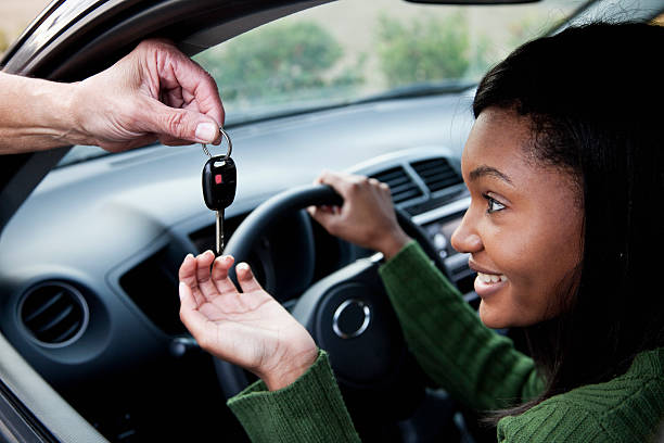Jeune femme dans une voiture qui prend les clefs de voiture qu'on lui tend avec un grand sourire