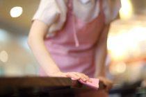 Gros plan sur une femme de ménage qui nettoie une table avec une microfibre