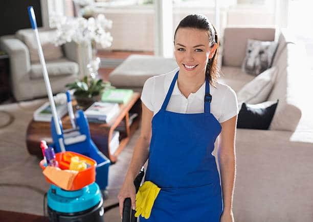 Jeune femme de ménage en tenue de travail avec ses produits ménagers