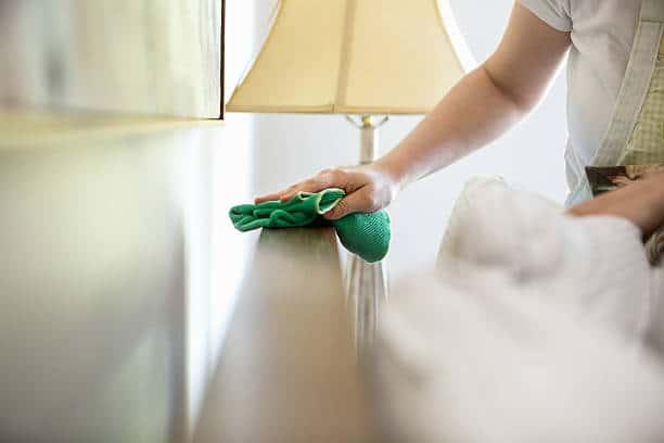 Femme de ménage qui dépoussière un meuble