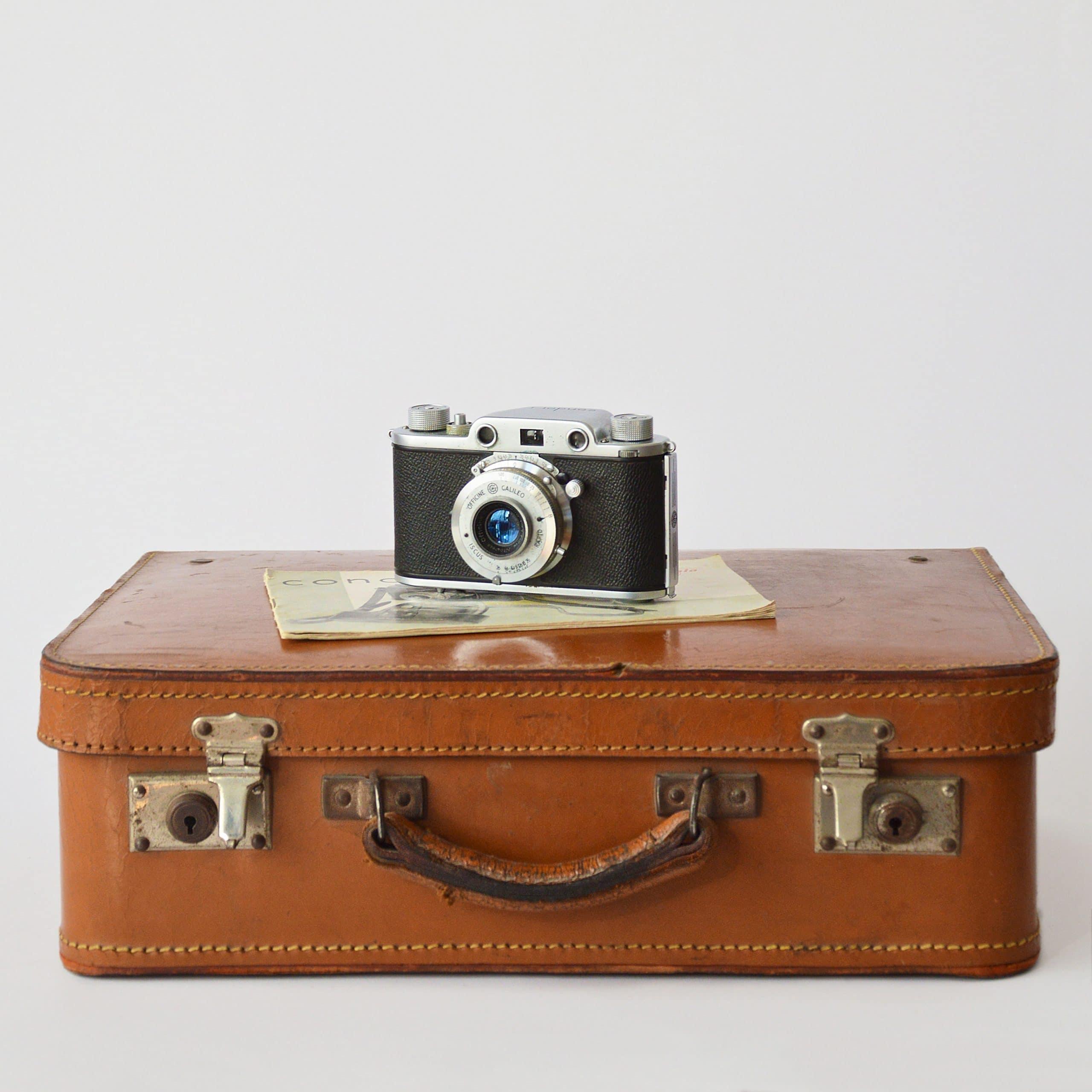 Valise en cuir avec appareil photo posé dessus