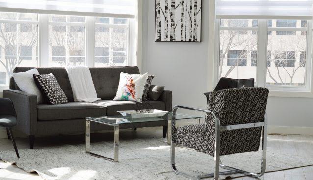 Salon moderne et lumineux avec fauteuil, canapé, table basse et tapis