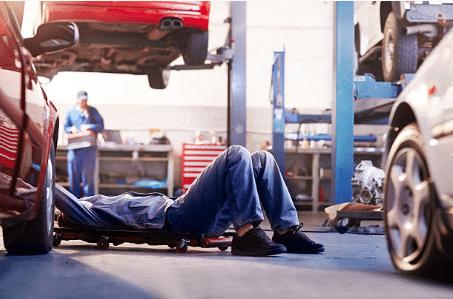 personne allongée qui répare une voiture
