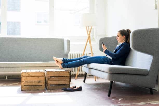 Femme assise dans son canapé avec les pieds sur sa table basse en cagettes