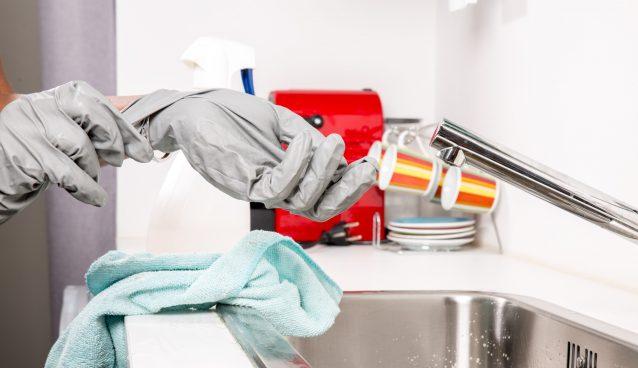 Personne qui retire des gants de ménage devant un évier
