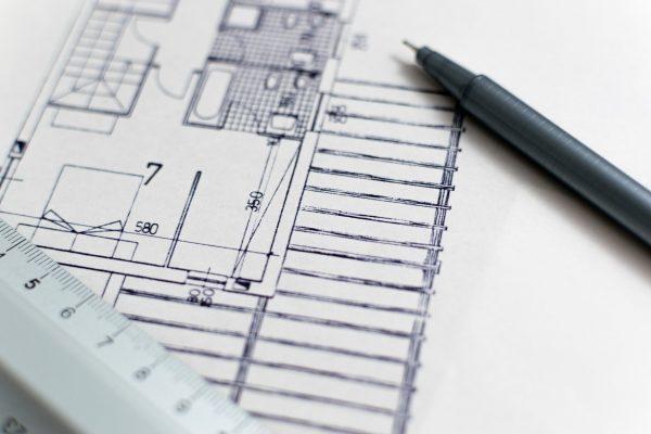 Zoom sur un plan d'architecte sur lequel sont posés un crayon et une règle