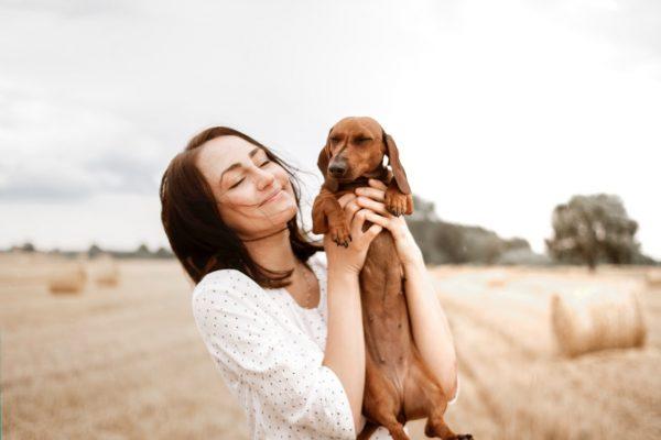 Femme qui prend un chien dans ses bras